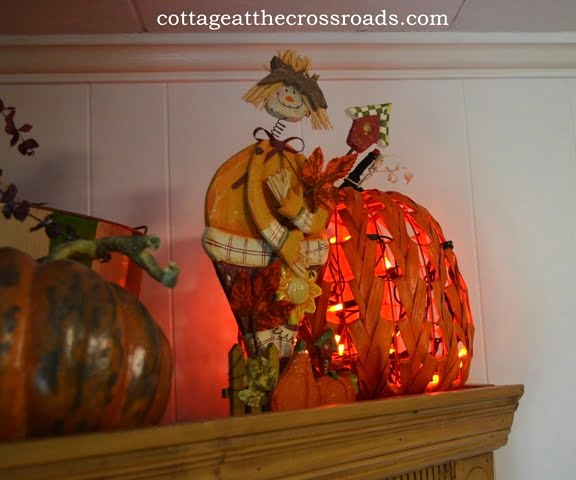 scarecrow and lighted pumpkin