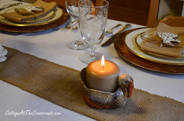 burlap runner with a turkey candleholder.