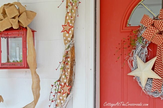 patriotic door display and decorated garland | Cottage at the Crossroads