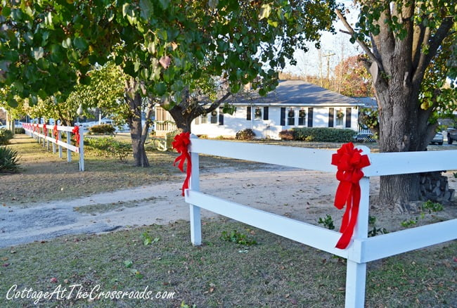 red bows on white fence | Cottage at the Crossroads