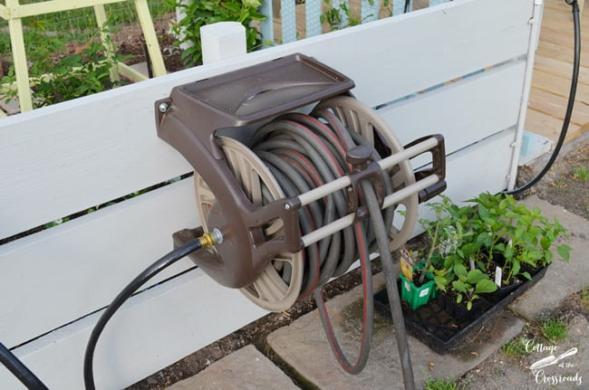 hose reel mounted on wooden boards in the garden | Cottage at the Crossroads