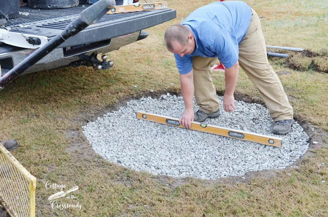leveling the pebbles in the base of Belgard fire pit install