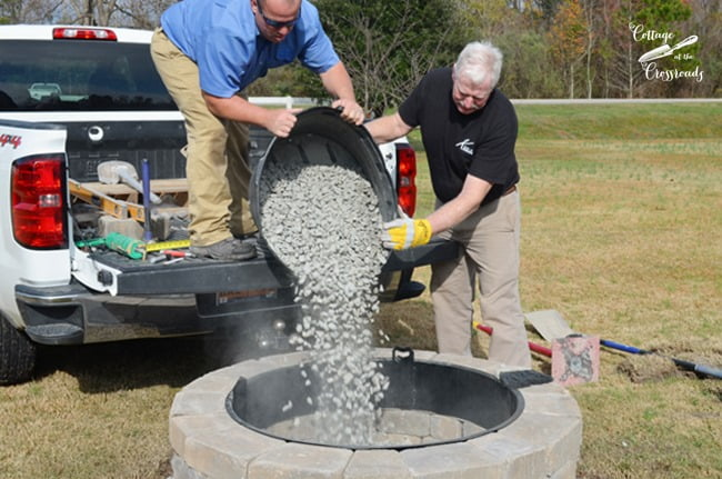 pouring pebbles into the Belgard fire pit