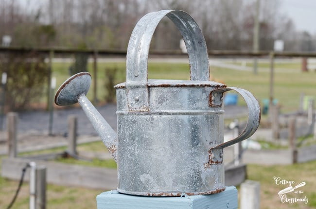 watering can on top of wooden garden trellis | Cottage at the Crossroads