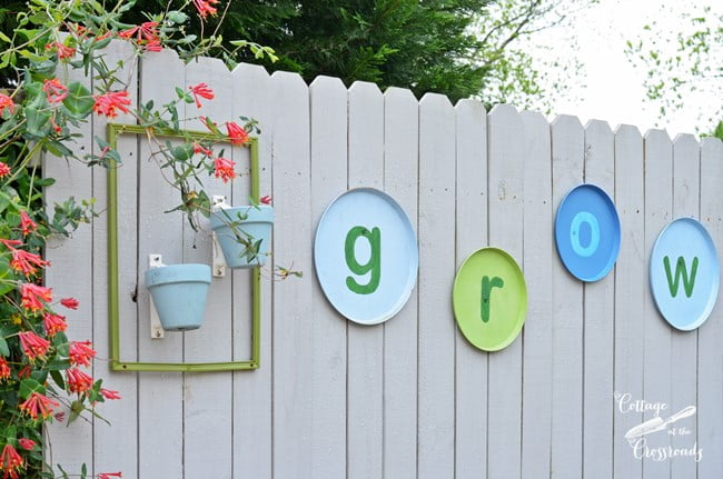 The word GROW hanging on wooden fence