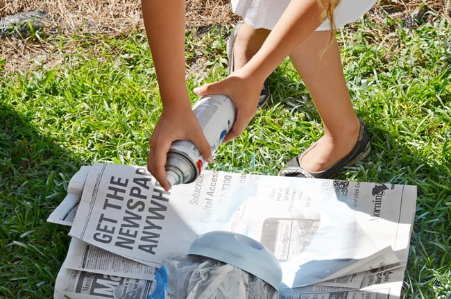 spray painting a top to a beach fairy garden