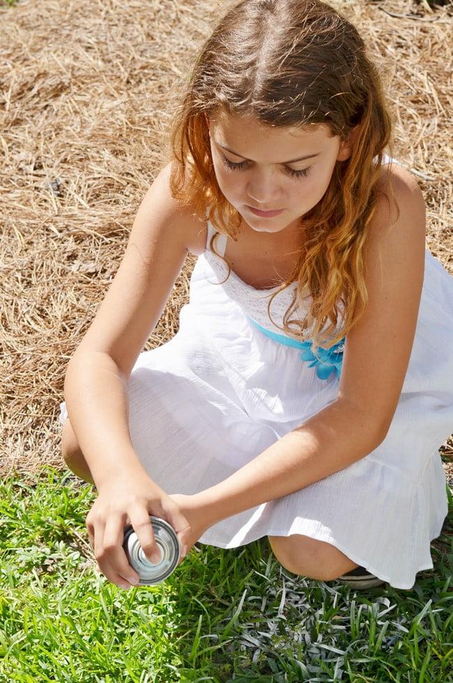 spray painting the top to a beach fairy garden