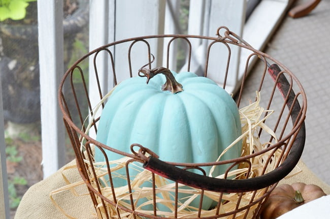 aqua pumpkin on an autumn decorated porch