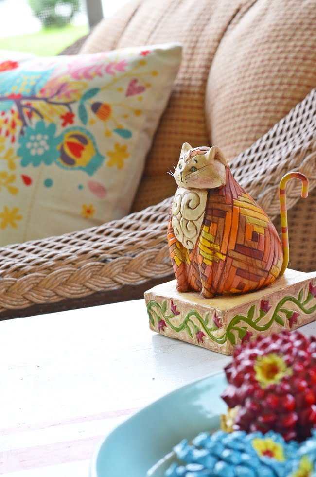 cat figurine on an autumn porch
