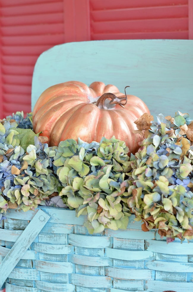 dried hydrangeas in a vintage picnic basket on a fall porch