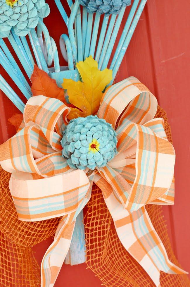 bow and pine cone zinnia on a fall rake wreath