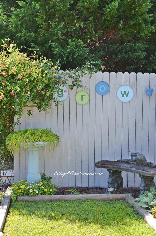 DIY Garden GROW sign on a wooden fence