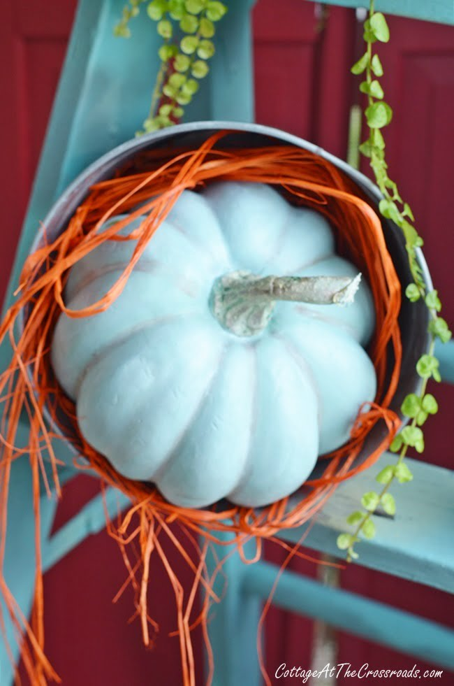 aqua faux pumpkin on a porch decorated for fall