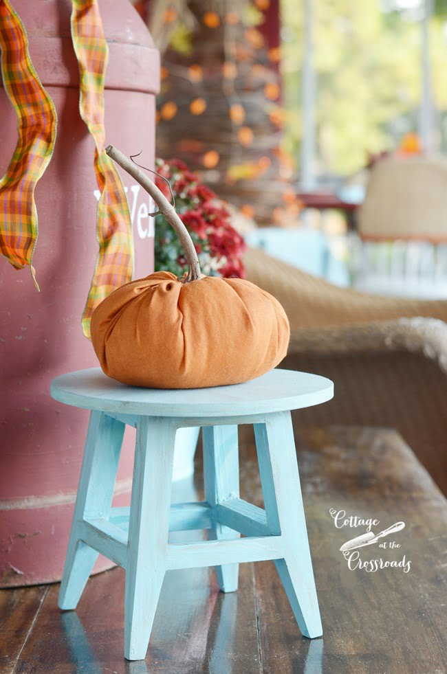 handsewn orange pumpkin on an autumn front porch