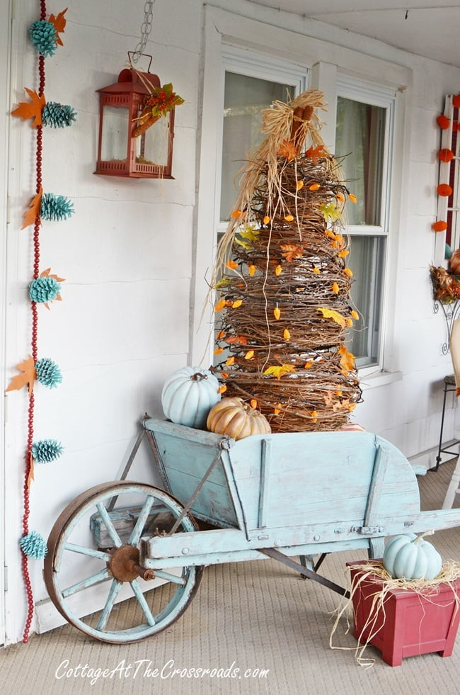 Handmade grapevine tree in an aqua wheelbarrow used on an autumn front porch