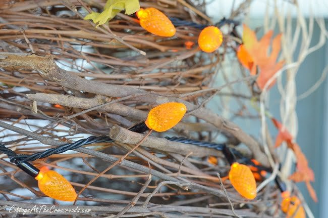 orange lights on a handmade grapevine tree used in decorating an autumn porch