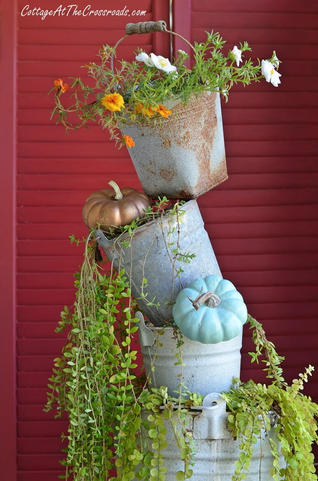 topsy turvy buckets on an autumn decorated front porch