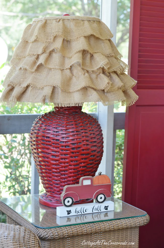 red wicker lamp with a burlap ruffled shade