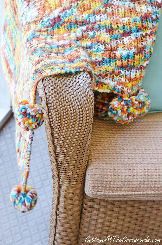 fall pom pom throw on an autumn porch
