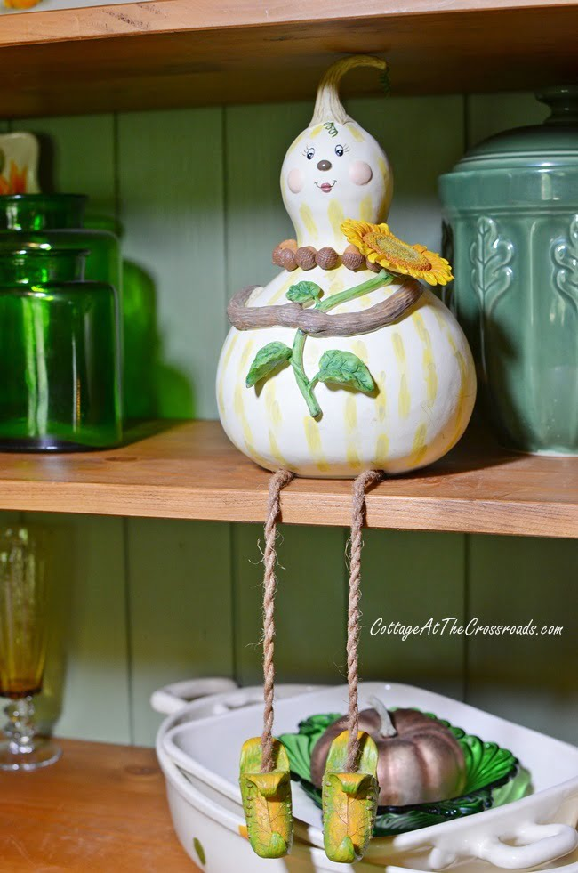 gourd lady on a fall decorated cupboard