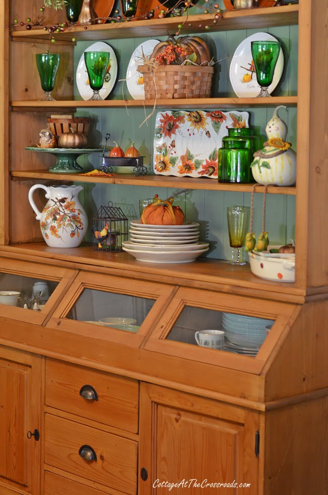 Pine farmhouse cupboard decorated for fall
