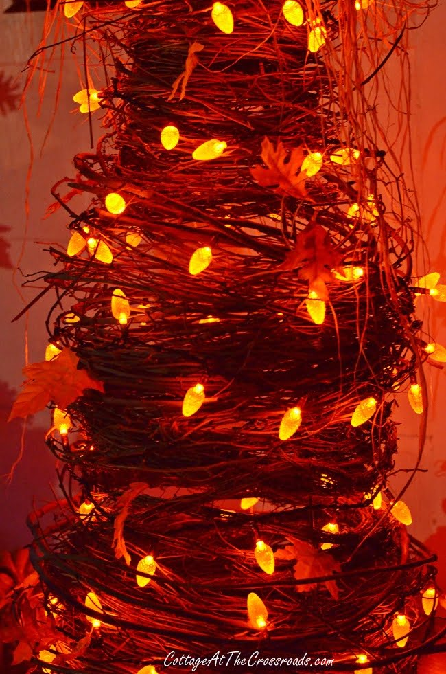 orange lights on a grapevine tree at night