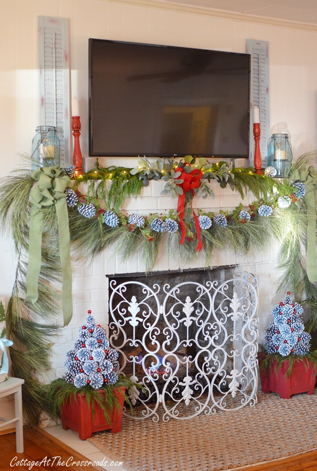 A Christmas mantel with pine cone trees at the base