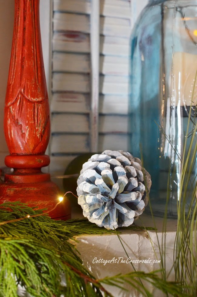 blue painted pine cone on a traditional Christmas mantel
