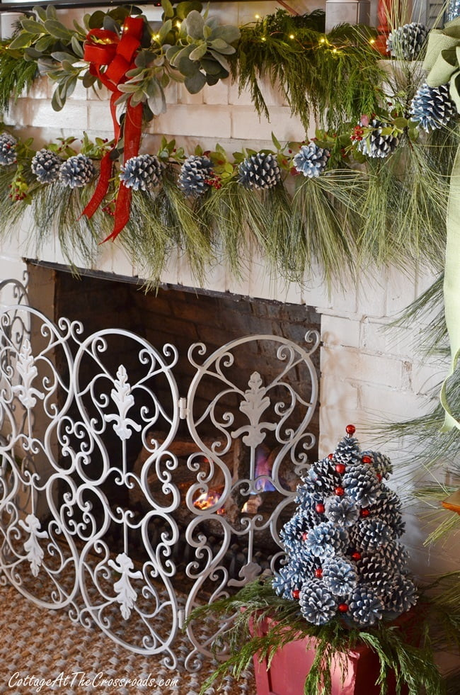 Christmas mantel decorated with painted pine cones