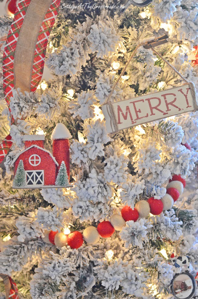 skinny flocked tree with red barn ornaments