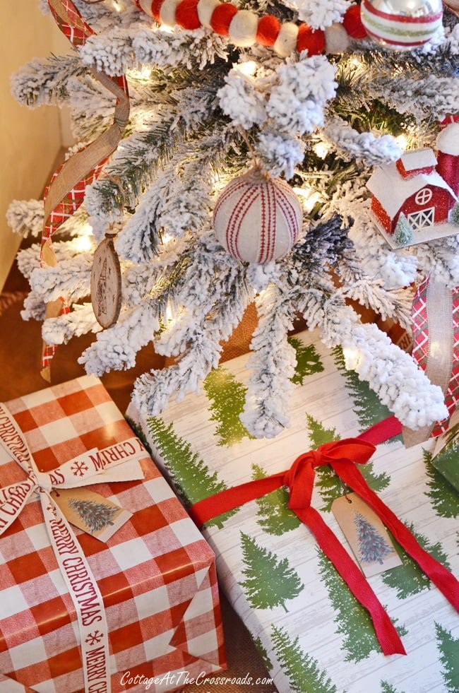 packages under a flocked Christmas tree