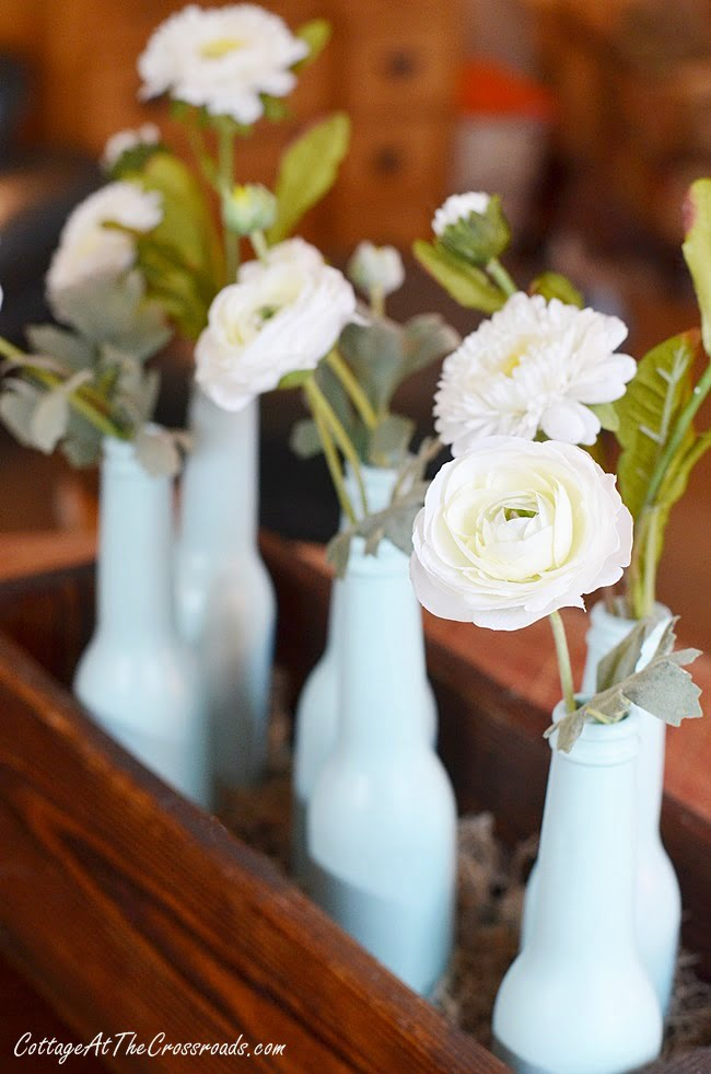 faux flowers in a painted bottle spring centerpiece