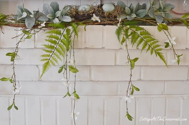 spring mantel with ferns and a blooming vine