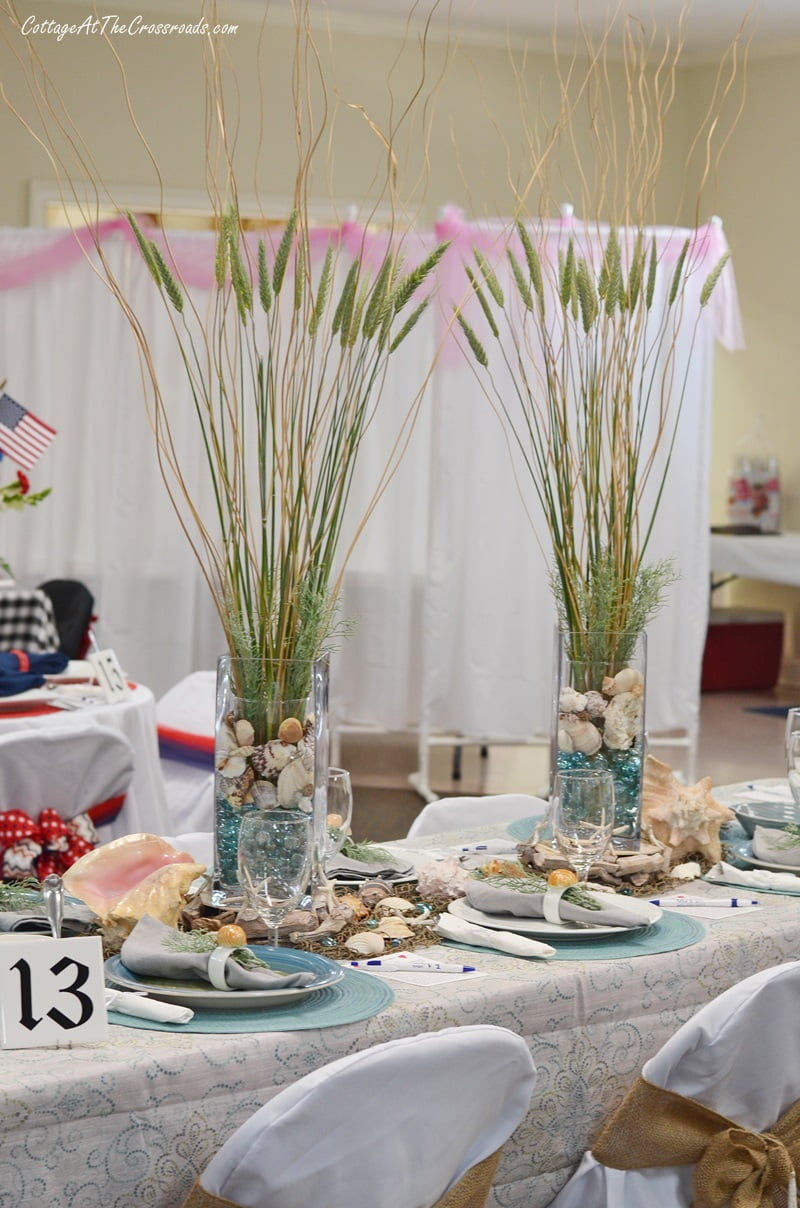tall grasses used as floral centerpieces in a coastal themed tablescape
