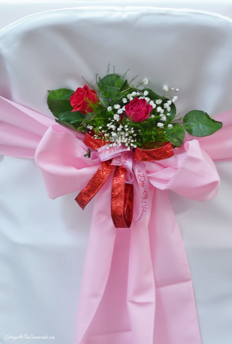 pink and red floral decoration on the back of chair covers at a Valentine's Day tablescape