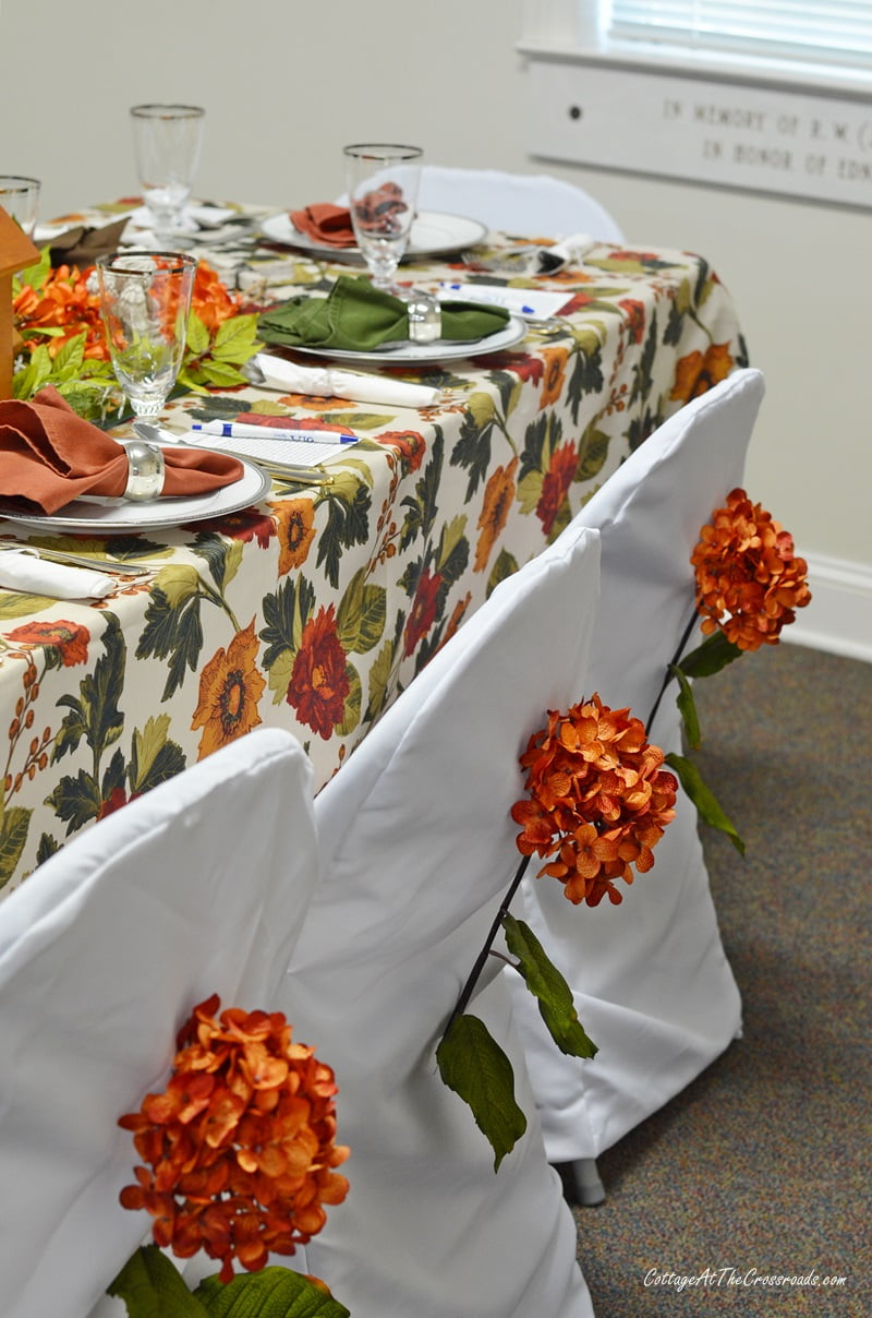 orange hydrangeas on chair backs at tablesetting fundraiser