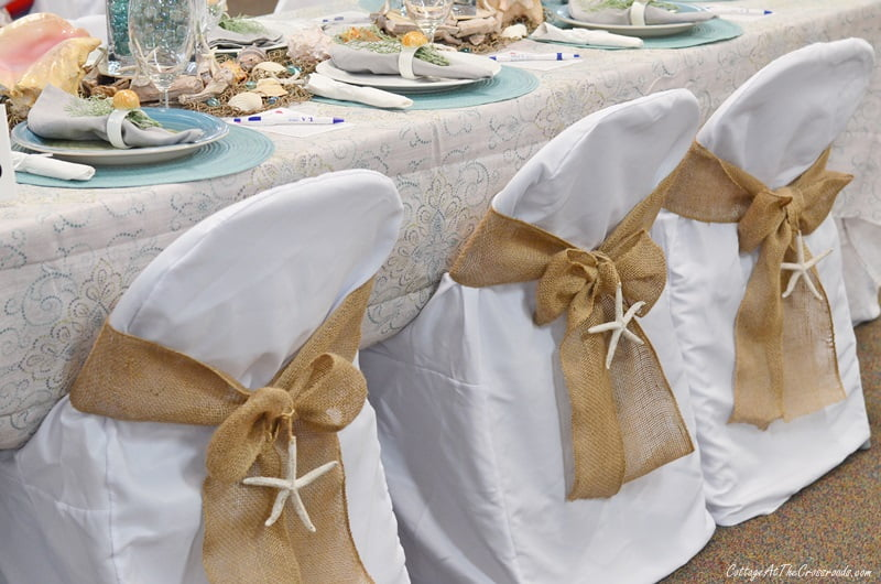 a coastal themed tablescape with chair covers decorated with starfish