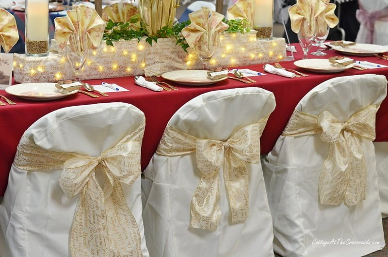 gold ribbon used on the backs of the chair covers at a tablesetting event