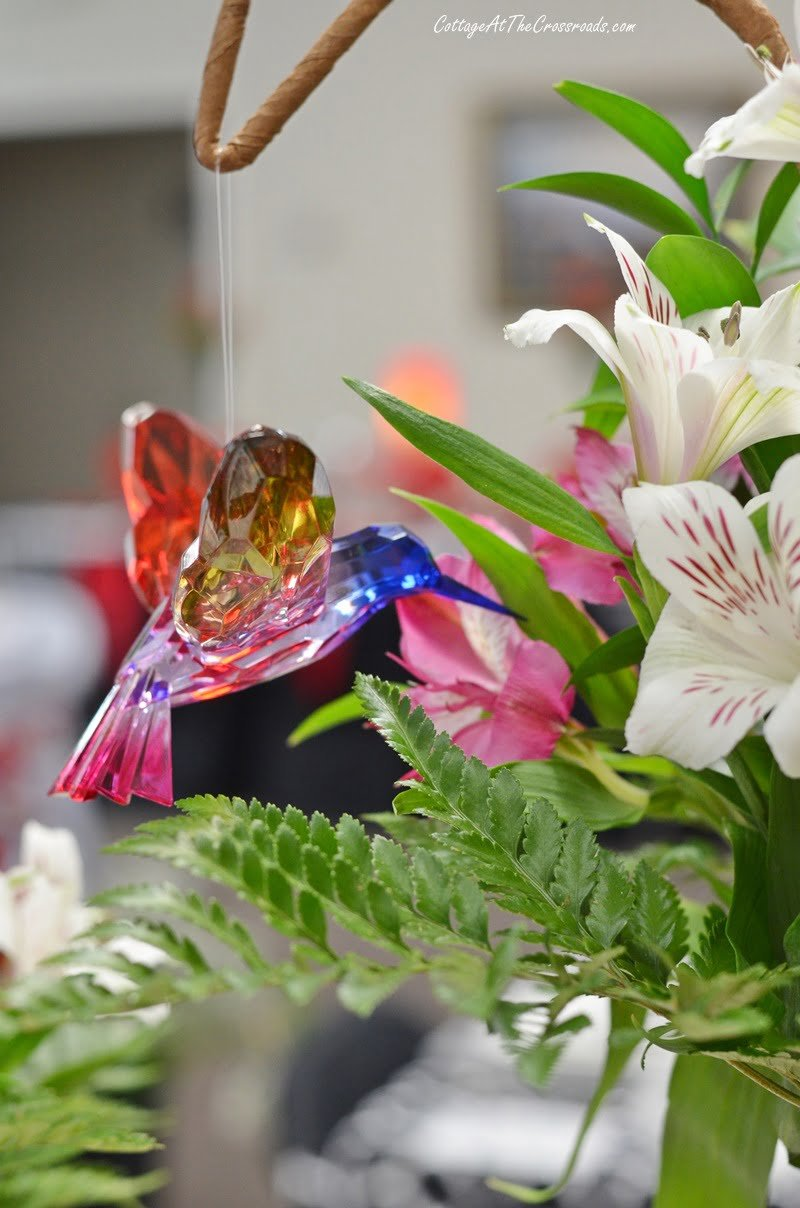 glass hummingbird hanging in a floral centerpiece