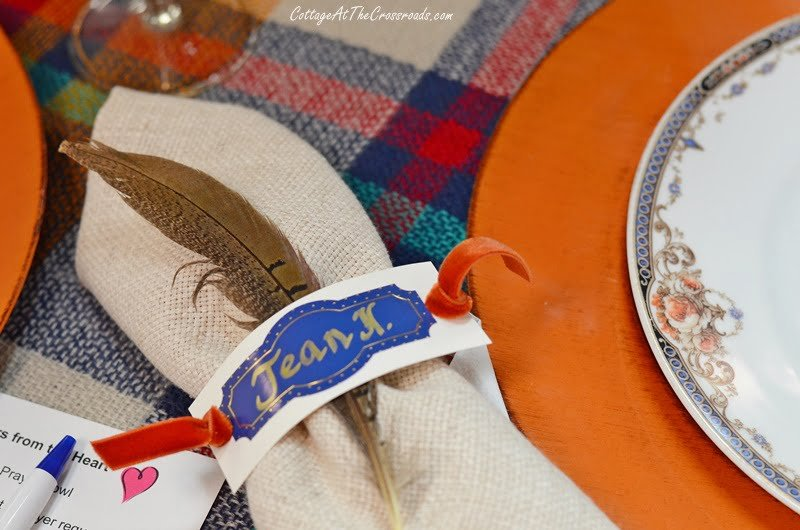 pheasant feather tucked into place card napkin ring