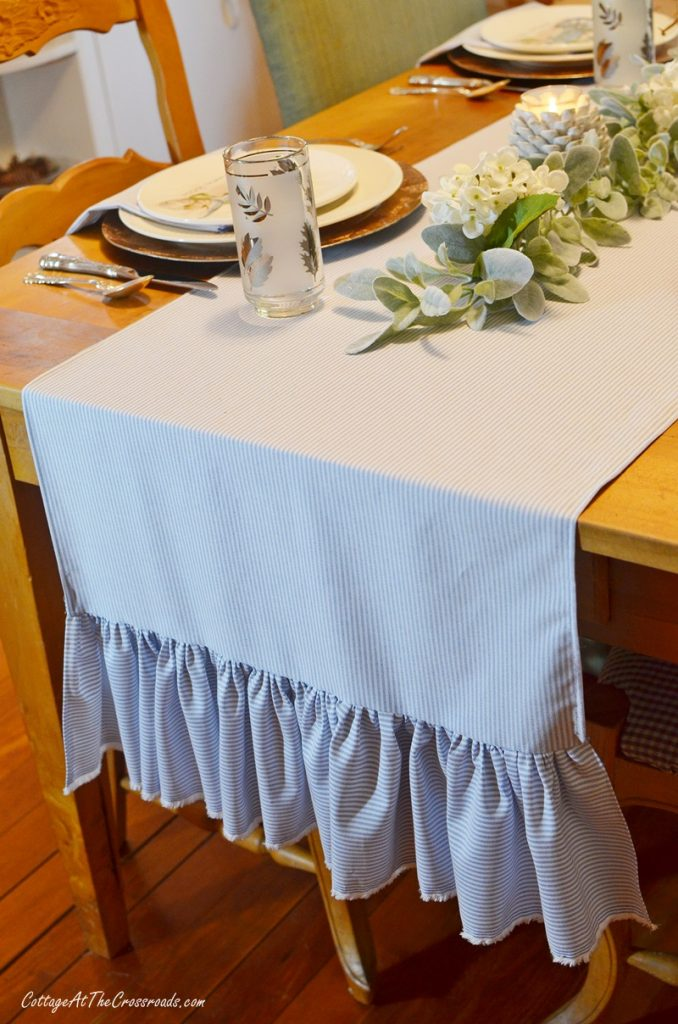 Thanksgiving tablescape using blue and white table runner with ruffled ends