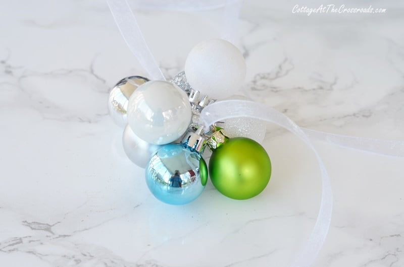 ornament balls threaded onto ribbon to make an ornament garland
