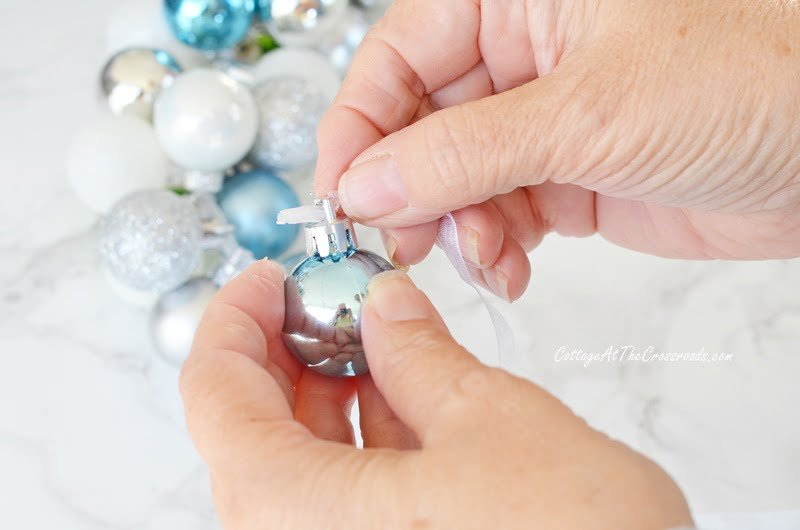 add tape at the end of the ribbon to help thread it through the ornament hanger