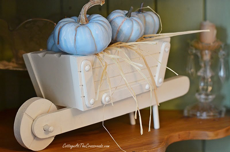 white wheelbarrow filled with blue pumpkins