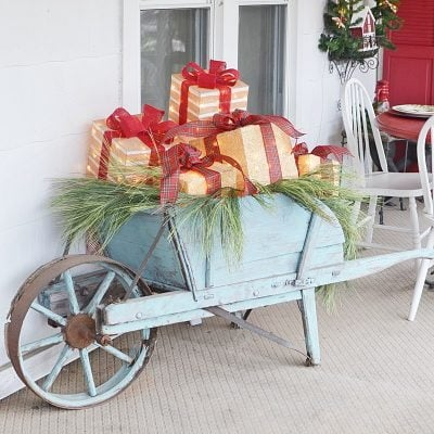 Festive Christmas Porch with a wheelbarrow loaded with lighted gifts