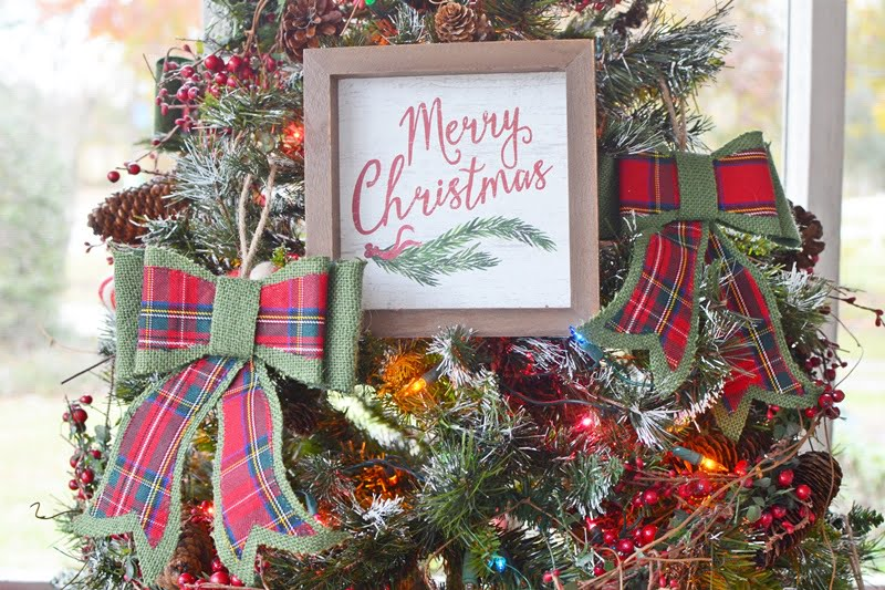 Merry Christmas wooden sign hanging on a Christmas tree