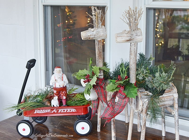 Santa in a red wagon on a Christmas front porch