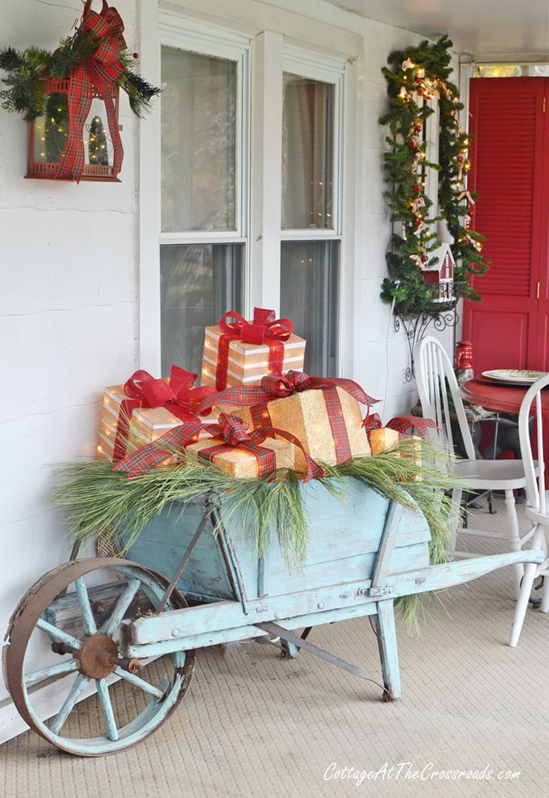 wheelbarrow filled with lighted boxes on a Christmas front porch