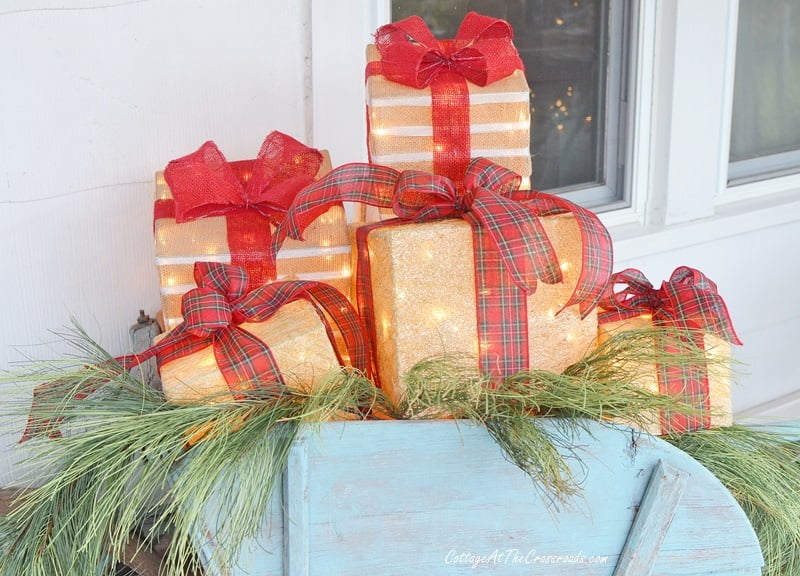 lighted gift boxes in a vintage wheelbarrow on a Christmas front porch