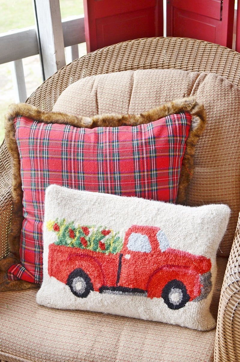 red truck and plaid pillows in a chair on a Christmas front porch